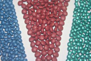 Sementes peletizadas formando faixas em cor azul, vermelha e verde